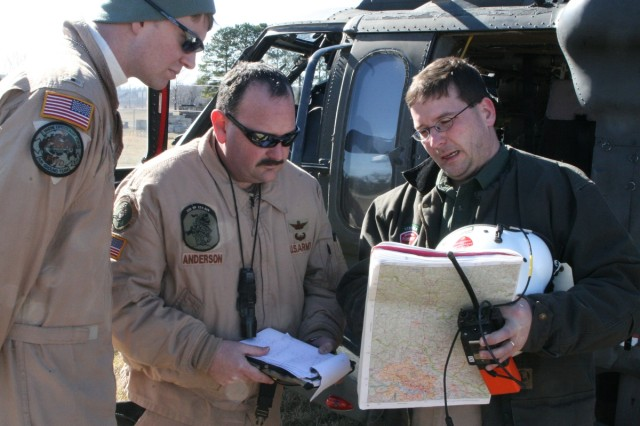 Two Virginia Army National Guard aviators, Warrant Officer Aaron Trombley (left) and Chief Warrant Officer John Anderson (center), check the location of their water drop on a Virginia wildfire Feb. 11 near Tazewell, Va., with Dave Slack of the Virginia Department of Forestry.