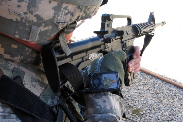 In a field demo at the Joint Readiness Training Center, Fort Polk, La., a Soldier demonstrates how the Vcommunicator iPod-sized translator device fits on the wrist but doesn't interfere with his weapon.
