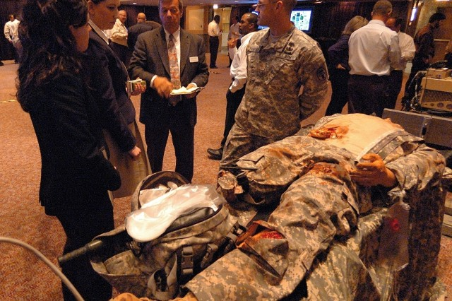 "Maj. Dave Thompson, assistant product manager for the medical simulation training center program at PEO-STRI explains how Soldiers are trained on the tethered ""breath-and-bleed"" mannequin."
