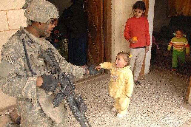 Spc. Hospedales gives candy to an Iraqi child during a patrol in Muqdadiyah. Hospedales is with Company B, 2nd Battalion, 23rd Infantry Regiment, 4th Brigade Combat Team, 2nd Infantry Division.