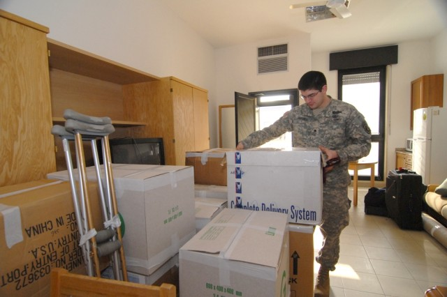 Sgt. Justin Varnes sets about unloading the boxes containing his belongings, as he moves into one of the new single rooms refurbished for Warrior Transition Unit barracks located in Vicenza, Italy.