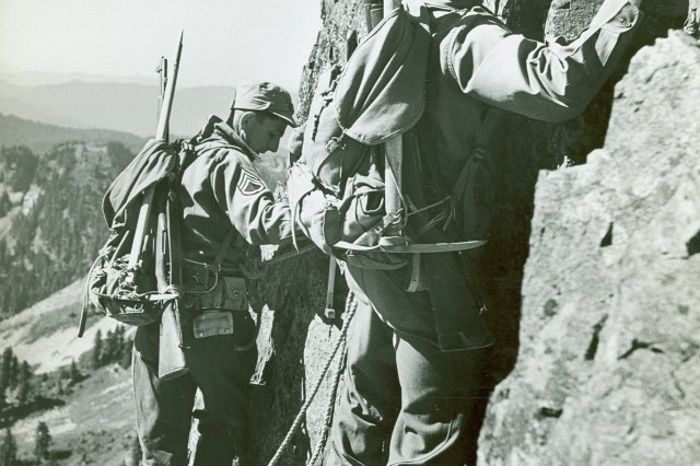 """Not quite leaping but still a super effort required of members of the 10th Infantry Divison in """"Horizontal Rock Traverse"""" training, c.a. 1942.  (Unit History Collection)."""