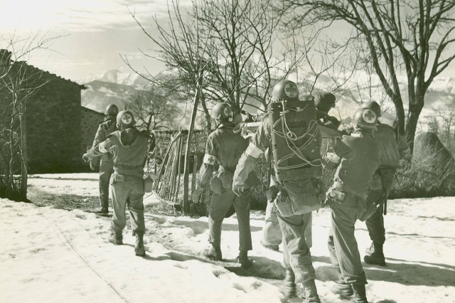 """""""20 February, 1945; Fifth Army, Mt. Belvedere,Italy, Walking wounded and a litter squad carry an enemy wounded Corporal cross an open snow field to the battalion aid station just under the crest"""" of the mountain. Mt. Belvedere was capture by the 10th Mountain Division. (Unit History Collection)."""