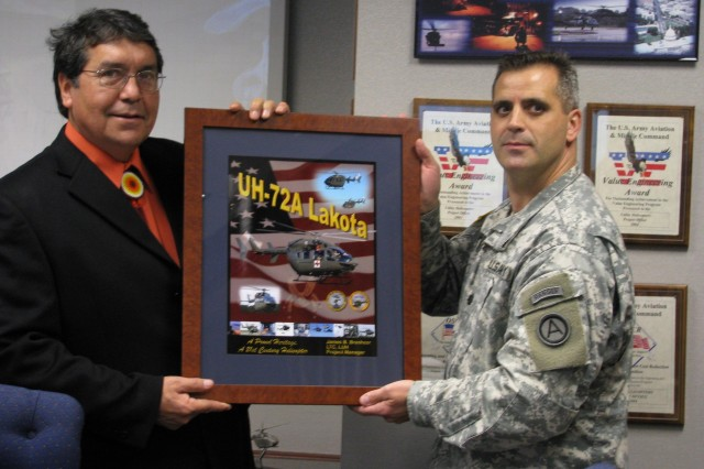 Rosebud Sioux tribal council president Rodney Bordeaux receives a Lakota UH-72A commemorative photo from Lt. Col. James Brashear, Light Utility Helicopter product manager.