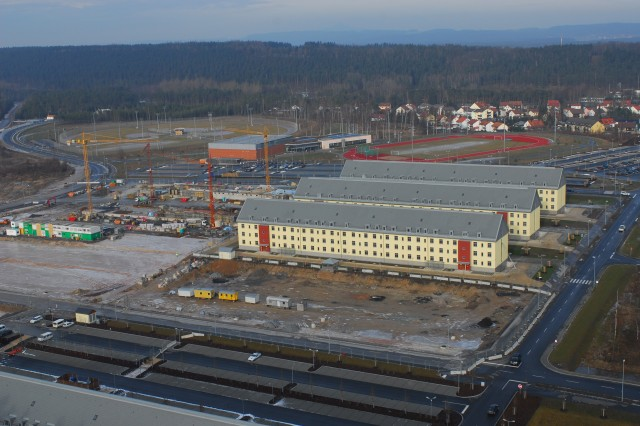 Three new and unoccupied barracks in Grafenwoehr, Germany, overlook cranes, backhoes, and cement trucks in January 2008 preparing the construction of two more new barracks, ideally positioned between the new physical fitness center, the new dining facility, and the PX/Commissary complex.