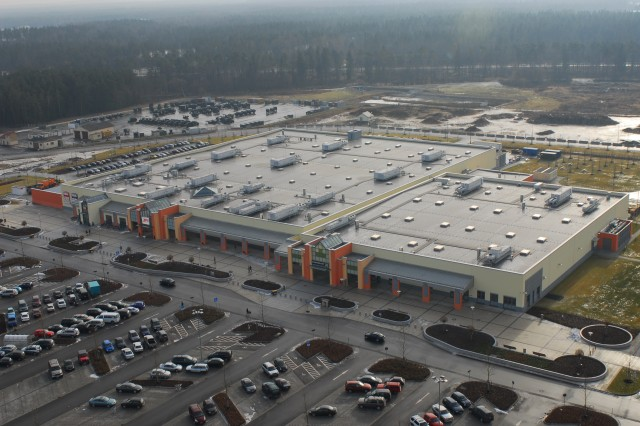 """A wet morning doesn't stop customers from shopping at Grafenwoehr's new, joint commissary/post exchange """"mall,"""" which, at almost 200,000 square feet, includes a bookstore, a 339-seat food court, a barber shop, a beauty shop, and space for 11 other concessionaires. The U.S. Army Corps of Engineers, Europe District, managed the construction of this project."""