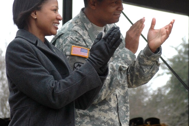 Outgoing 15th Sustainment Brigade commander Col. Aundre Piggee and his wife Kassi Piggee watch for the last time as Soldiers of the 15th SB march by during the ceremony's pass and review.