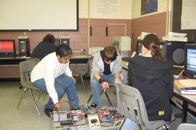 Yolanda Hinton, left, works with students at Menchville High School where she serves as a mentor for a robotics team established by ARL's Vehicle Technology Directorate.