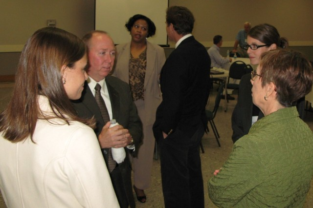 At the Anniston City Meeting Center, the depot's deputy to the commander, Jack Cline (second from left), greets Betsy Bean (right), Spirit of Anniston's executive director, at the Feb. 12 sustainability workshop. Mary Frances Smith (far left) and Charlotte Pugh (second from right) with the consulting firm CH2M HILL helped facilitate the three-day workshop. Pictured in the back are Tracy Williams and Calhoun County Commissioner Robert Downing.