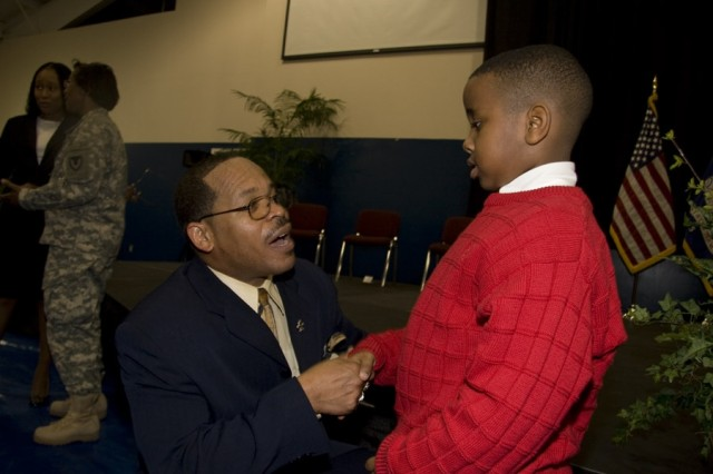 """Dr. Danna Andrus, keynote speaker at the Black History Month luncheon, applauds seven-year-old Brenton Ball, who delivered excerpts from Dr. King's """"I Have a Dream"""" speech."""