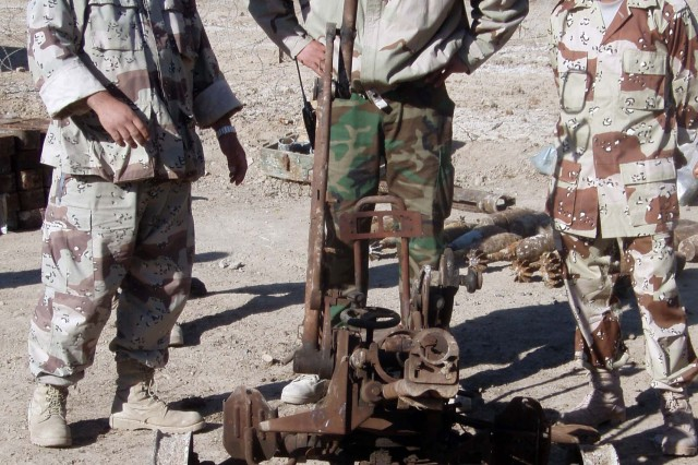 Iraqi Army Soldiers talk about a towed gun mount found in a weapons