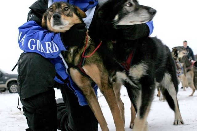 Rodney Whaley hugs two of his sled dogs.