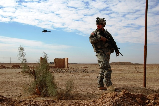 A 1st Brigade Combat Team, 101st Airborne Division (Air Assault) Soldier keeps a watchful eye while on a desert patrol with assistance from a Kiowa Warrior aircraft outside of Samarra, Iraq during Operation Iraqi Freedom.