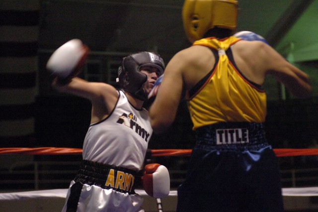 Army National Guard Sgt. Cherrie Retamozzo (left) of Staten Island, N.Y., throws a right hook during her 34-11 victory over UT2 Sonia Deputee of Naval Base Ventura County in Port Hueneme, Calif.
