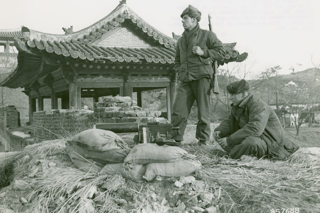 Korean Conflict - Cpl. Donald C Blackman of Longsport, ID (sitting), and Cpl. Joseph L. Lasleur of Stillman, Valley, IL, keep a sharp lookout for Chinese Communists troops at their post near the front lines in Korea.  Both are members of the 27th Infantry Regiment, 25th Infantry Division. January 29th, 1951.