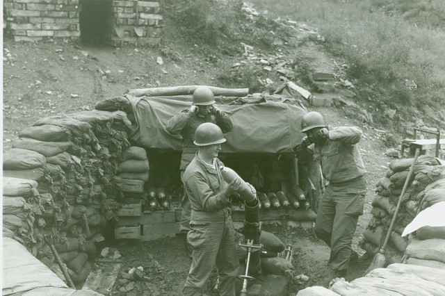 Korean Conflict - Men of the 2nd Platoon, Heavy Mortar Company, 14th Infantry Regiment, 25th US Infantry Division, fire mortar shells at Communist-held positions from their post on Hill #719, Heartbreak Ridge.  September 27th, 1952.