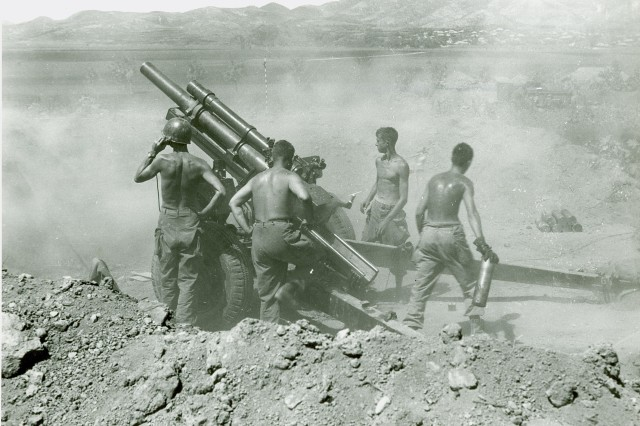 Korean Conflict - Gun Crew of the 25th Infantry Division fire a 105mm howitzer on North Korean positions, near Uirson, Korea. August 27th, 1950.