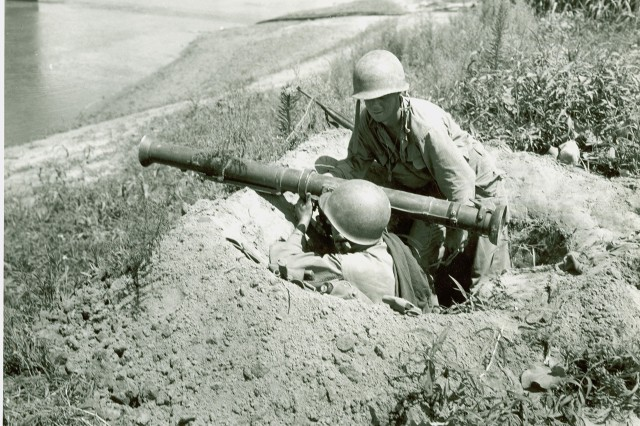 Korean Conflict - Pfc. Earl L. Whennen of Ottumwa, LA, and Pvt. Richard A. Stevenson of Berwyn, Ill, man a rocket launcher covering a possible North Korean approach on a river, somewhere on the Korean front lines.  August 4th, 1950.
