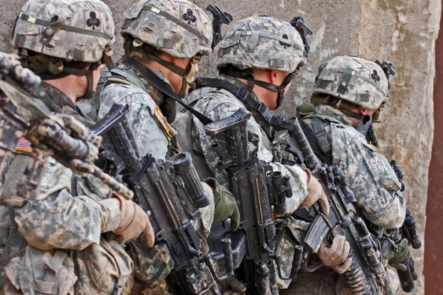 Soldiers with the 1st Squadron, 32nd Cavalry Regiment, 1st Brigade Combat Team, 101st Airborne Division (AA), prepare to enter and clear a building near the Bichigan peninsula of the Salah ad Din province, Iraq.