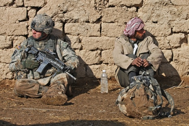 A Soldier from 1st Squadron, 32nd Cavalry Regiment, 1st Brigade Combat team, 101st Airborne Division (AA) sits with an Iraqi man near the Bichigan peninsula.