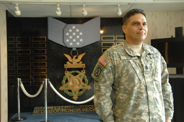 Quartermaster Regimental Command Sgt. Maj. Jose L. Silva, U.S. Army Quartermaster Center and School, stands next to his favorite spot, the Quartermaster Corps Medal of Honor Recipients display at Mifflin Hall. Silva retires from the Army March 4 after more than 25 years of service.