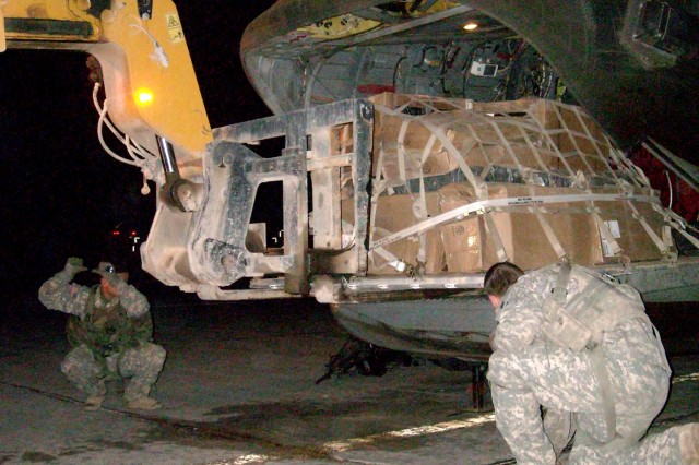 Soldiers from the 12th Combat Aviation Brigade's Company B, 5th Battalion 158th Aviation Regiment oversee the loading of a pallet on the back of a CH-47 Chinook helicopter at Logistical Support Area Anaconda in Balad, Iraq, in preparation for a cargo mission.