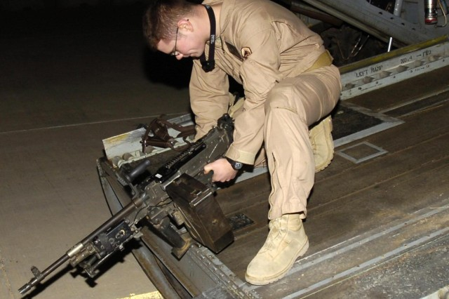 Spc. Cameron Randall, a door gunner attached to the 12th Combat Aviation Brigade's Company B, 5th Battalion, 158th Aviation, installs a machine gun on the back gate of a CH-47 Chinook helicopter at Logistical Support Area Anaconda in Balad, Iraq.