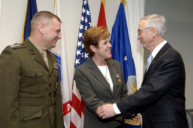 Deputy Secretary of Defense Gordon England congratulates Carol King, Army Material Command, following presentation of the Secretary of Defense Medal for the Global War on Terrorism during a Pentagon ceremony Feb. 26.  Looking on is USMC Gen. James E. Cartwright, vice chairman of the Joint Chiefs of Staff.    DoD photo by R. D. Ward
