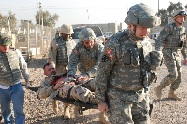 Students carry a casualty to an ambulance during the mass casualty event for the combat lifesaver course. 