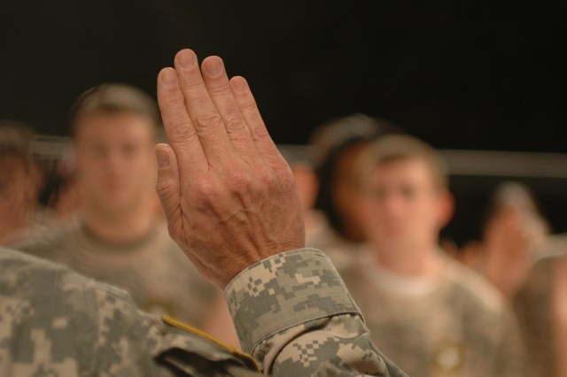 Brig. Gen. Daniel I. Schultz's hand is raised as he states the oath of enlistment and swears in 20 recruits March 2.
