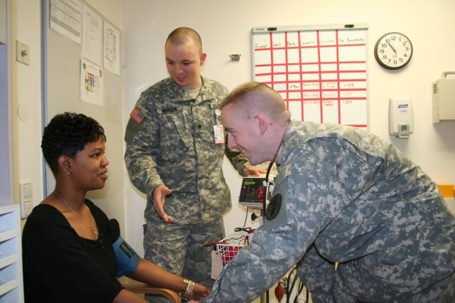 Sgt. Jamerson Hayward, listens to instructions from Spc. Donald Heitger, an Army medic, while taking Kyshone Moss' blood pressure at the U.S. Army Health Clinic Bamberg. Hayward, a soldier in the Warrior in Transition Unit, is training to assist at the clinic.