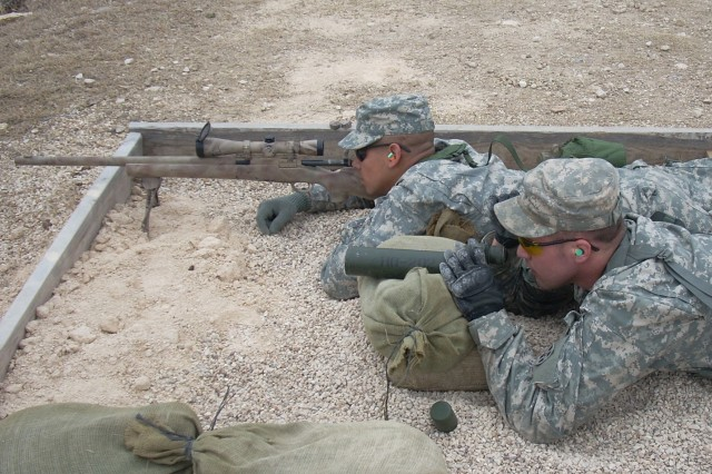 A Soldier, assigned to 3rd Battalion, 67th Armored Regiment's headquarters company, prepares to fire the M24 sniper rifle while Sgt. Michael Potter, also with the headquarters company, serves as his spotter.