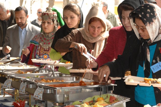 Members of the Afghan community line up for lunch at the International Women's Day event celebrating the world's women and acknowledging women's contributions to peace and security at Bagram Airfield March 3.