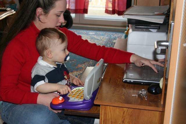 Samantha Windell and her 14-month-son Damion check for messages on their computer from their husband and father Spc. Chase Windell.