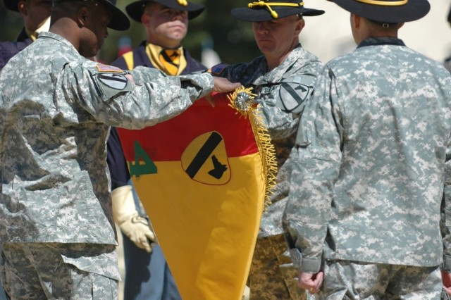 Col. Stephen Twitty, commander of the 4th BCT, 1st Armd. Div. (left) and Command Sgt. Maj. Stephan Frennier case the 4th Brigade Combat Team, 1st Cavalry Division during a noon reflagging ceremony Wednesday at Noel Field.