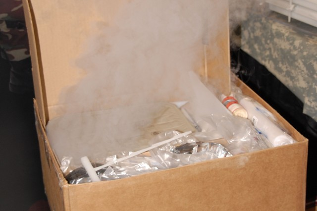 """The """"Unitized Group Ration - Express"""" provides hot meals for up to 18 Soldiers.  The ration is a completely self-contained feeding system, requiring no additional equipment, heat or water.  By pulling a tab on the unit, a Soldier releases a saline solution into the container that activates heaters similar to those found in the MRE. In as little as 30 minutes, Soldiers have a hot meal. The UGR-E is designed for Soldiers serving in remote locations or at a forward operating base."""
