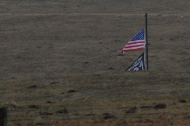 The American flag and Prisoner of War flag are visible just over a hill on Frank Buckles' farm in West Virginia. In addition to serving in the U.S. Army during World War I, he was a civilian prisoner of war of the Japanese in the Philippines in World War II.
