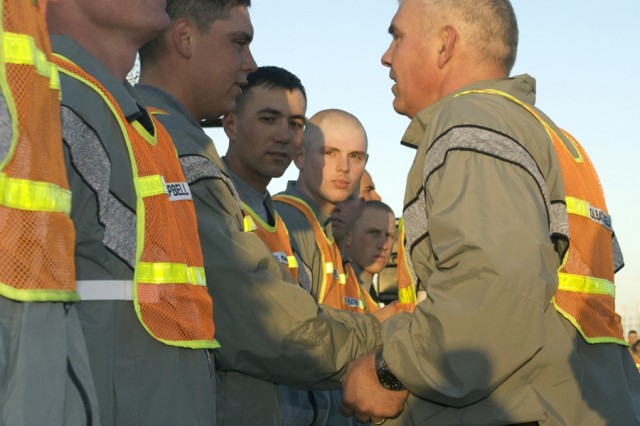 Col. Philip Battaglia, the commander of the 4th Brigade Combat Team, presents Soldiers with some of the last 4th BCT, 4th Infantry Division, challenge coins during a presentation following a brigade run March 5. The 4th BCT re-flagged to become part of the 1st Cavalry Division March 7.