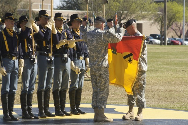 Col. Philip Battaglia, the 4th Brigade Combat Team commander, and Brigade Command Sgt. Maj. Edwin Rodriguez unveil their brigade's new colors during the Long Knife Brigade's re-flagging ceremony at 1st Cavalry Division's Cooper Field on Fort Hood, Texas, March 7.