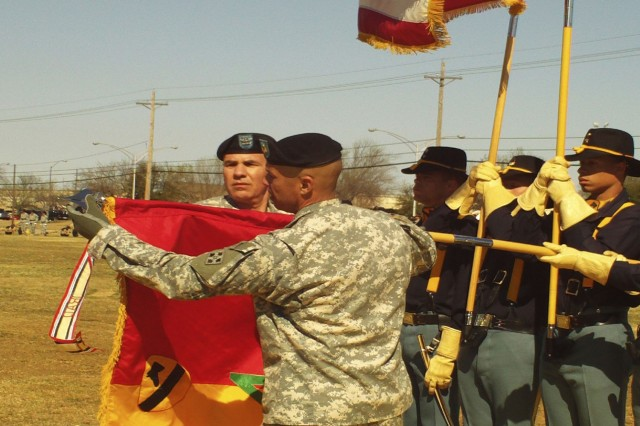 Col. Philip Battaglia, the 4th Brigade Combat Team commander, and Brigade Command Sgt. Maj. Edwin Rodriguez unveil the new brigade colors during the unit's re-flagging ceremony at 1st Cavalry Division's Cooper Field on Fort Hood March 7.