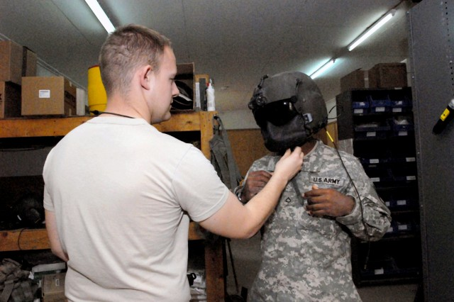 Sgt. David Shafer, NCO-in-charge of the Aviation Life Support Equipment shop at Camp Taji, Iraq (left), shows a Soldier the proper way inspect his flight helmet. The ALSE shops at Taji and Logistical Support Area Anaconda in Balad, operated by units of the 5th Battalion, 158th Aviation, are responsible for maintaining equipment for nearly 500 aviators.