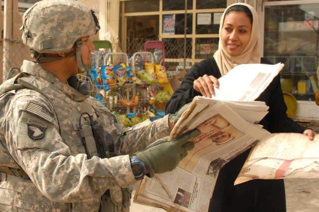 "Sgt. Jamie Rivas, from the 312th Tactical Psychological Operations Company, hands out an issue of the ""Baghdad Now"" newspaper to an Iraq lady in the Rashid district of Baghdad."