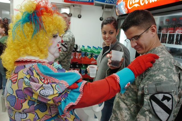 Mayjane DeBee from Houston, places a sticker on Spc. Wilmer Alverio, an Apache mechanic with the 3rd Battalion, 227th Aviation Regiment, 1st Air Cavalry Brigade, 1st Cavalry Division, as his wife Erika watches at a Soldier appreciation day hosted by the Copperas Cove Chamber of Commerce March 10. Mayjane entertained Soldiers and Soldiers' children with her clown costume and stuffed animals during the event.