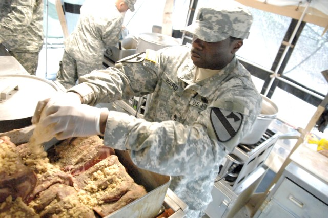 Staff Sgt. Andre Ward, Fort Bliss, worked within the confines of the mobile kitchen trailer on what was a cold and rainy day in the field during the Armed Forces Field Kitchen Event March 7 at the 33rd U.S. Army Culinary Arts Competition at Fort Lee, Va. The field competition is designed to test field cookery skills and teamwork utilizing the mobile kitchen trailer. Photo by Mike Strasser, Fort Lee Public Affairs Office