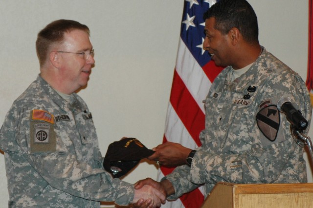 Brig. Gen. (P) Vincent K. Brooks, the 1st Cavalry Division's commanding general (left), gives Chaplain (Brig. Gen.) Donald L. Rutherford a Cav hat and a plaque to thank him the  serve themselves breakfast at the 1st Cav. Div.'s Welcome Home Prayer Breakfast at the Fort Hood Conference and Catering Center March 11.