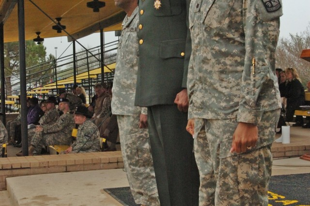 (From left to right) Col. Bryan Roberts, the commander of the First Team's 2nd Brigade Combat Team, retired Sgt. Maj. Larry Warren, the 1st Cavalry Division's former G6 top noncommissioned officer, and Cadet Crystal Warren with the 712th Military Police Company, a National Guard unit operating out of Baytown, Texas, stand at attention as the First Team band play in honor of the retiree's 30 years in the Army in front of Fort Hood, Texas's Cooper Field March 11.