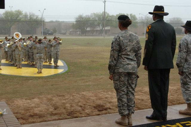 (From left to right) Cadet Crystal Warren with the 712th Military Police Company, a National Guard unit operating out of Baytown, Texas, Sgt. Maj. Larry Warren, the 1st Cavalry Division's former G6 or information management top noncommissioned officer, and Col. Bryan Roberts, the commander of the First Team's 2nd Brigade Combat Team, listen to the band play tribute to Sgt. Maj. Warren's 30 years of dedicated service to the Army during a ceremony held on the division's parade field on Fort Hood, Texas, March 11.