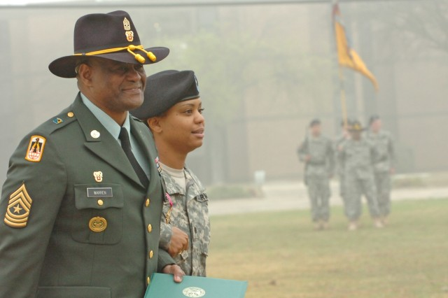 Retired Sgt. Maj. Larry Warren, 1st Cavalry Division's former G6 top noncommissioned officer, and his daughter Cadet Crystal Warren with the 712th Military Police Company, a National Guard unit operating out of Baytown, Texas, walk off of the division's parade field during a Distinguished Service and Welcome ceremony held on Fort Hood, Texas's Cooper Field March 11.