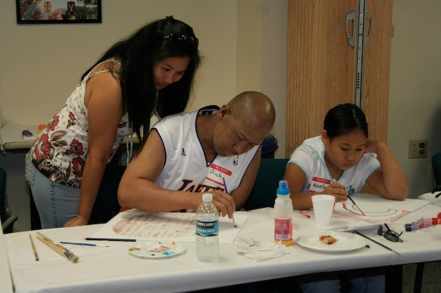 Influenced by his cancer journey, Ricky Lumang paints with daughter Rizelle, while wife Marilyn looks over his shoulder March 8 at Tripler Army Medical Center.  Courtesy photo by Jerry Quimby.