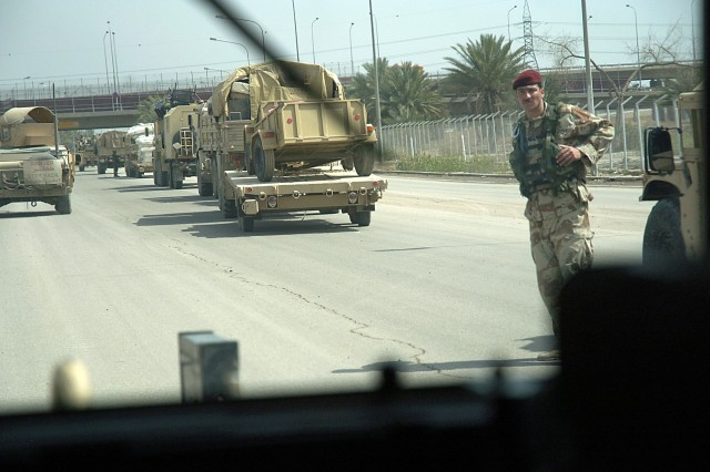 An Iraqi army soldier looks on as the crew of 2nd Section, 2nd Platoon, Headquarters Support Company, Task Force Dragon, Fort Bragg, N.C. pass by on the streets of Baghdad March 13.  The HSC Soldiers took more than 50 passengers safely to their destination while conducting convoy security that day.
